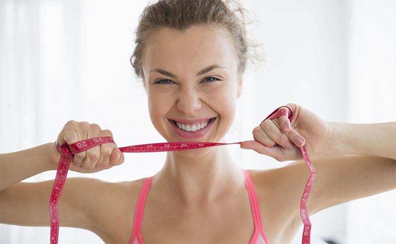 spalacze tłuszczu efekty stosowania, uśmiechnięta kobieta z miarką